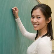 Woman Chinese Teacher in Front of Blackboard