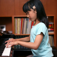 Asian girl playing upright piano