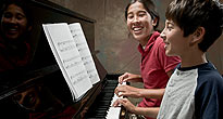 Female piano teacher and boy student laughing