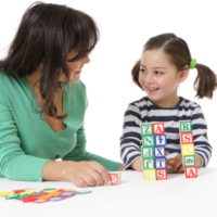Female teacher playing with blocks with little girl