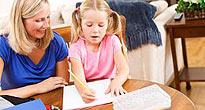 Female teacher helping little girl with homework